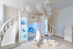 inre av ett rymligt rum för barn` s dekorativ slott med säng inom, den modiga glidbanan och trappa Royaltyfria Foton