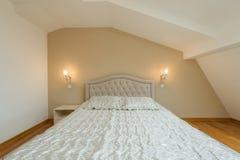 Inre av ett vindsovrum med ledar- säng i lyxig lägenhet arkivfoto