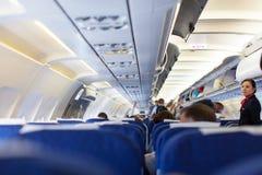 Inre av flygplanet med passagerare på platser som väntar på, tar av Royaltyfria Bilder