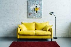 Inre av hemtrevlig vardagsrum med målning på väggen, soffan och golv royaltyfri fotografi