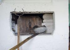 Inre av köket i gammalt byhus med den traditionella tegelstenugnen värmde vid trä och kitchenware för att förbereda mål i royaltyfria bilder