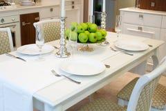 Inre av klassiskt vitt kök- och äta middagområde; tjänad som tabell för 4 personer; frukt; äpplen; vitstearinljus Arkivbild