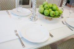 Inre av klassiskt vitt kök- och äta middagområde; tjänad som tabell för 4 personer; frukt; äpplen; vitstearinljus Arkivbilder