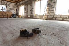 Inre av lägenheten under under-renovering, att omdana och konstruktion per par av funktionsdugliga skor på cementet däckar Arkivfoton