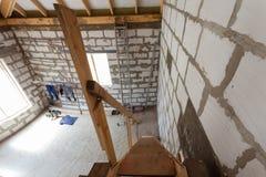 Inre av lägenheten under under-renovering, omdana och konstruktionsträtrappa till första golv- och arbetarkläderna Arkivbild