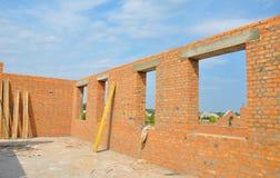 Inre av oavslutade väggar för ett hus för röd tegelsten under konstruktion, utan att taklägga Arkivfoto