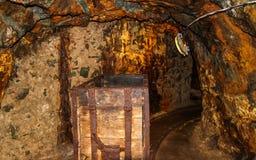 Inre av passagen för underjordisk min med stänger, ljus och vagnen Fotografering för Bildbyråer