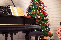 Inre av rum med piano- och granträdet Julfilial och klockor Arkivbild