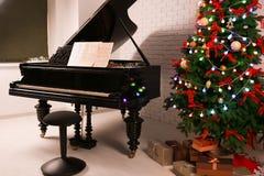 Inre av rum med piano- och granträdet Julfilial och klockor Arkivfoto
