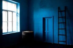Inre av rummet med det blåa väggfönstret utan gardiner och trappa arkivfoton
