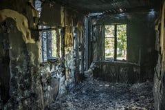 Inre av som bränns av brandlägenheten i en hyreshus Brända träväggar Arkivbild