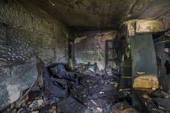 Inre av som bränns av brandlägenheten i en hyreshus, bränt möblemang Royaltyfria Bilder