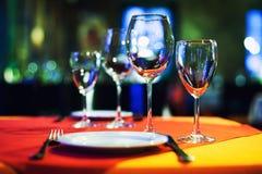 Inre bakgrund för romantisk kaférestaurang som tjänas som tabell tomma vinexponeringsglas, vit platta och bestick Ljust suddigt Fotografering för Bildbyråer