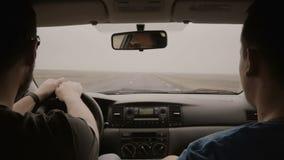 Inre bil för sikt Resande för två man med bilen till och med landsvägen Man i solglasögon som kör bilen och talar med vännen lager videofilmer