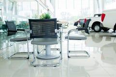 Inre bilvisningslokalinre med gruppen av stolar och tabellen royaltyfri bild