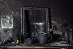 Inre bränt rum Bränd stilleben Den brände till kol väggen, bildramen, kruka med bränt steg i svart sot royaltyfri bild