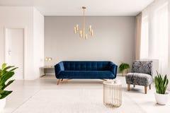 Inre för kopieringsutrymmevardagsrum med ett mörker - blå soffa, en grå fåtölj och guldbrytningar Verkligt foto arkivfoton