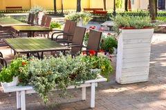 Inre för sommargatakafét i grön stad parkerar, utsmyckat med blommor och dekorativa beståndsdelar Arkivfoton