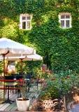 Inre för sommargatakafét i grön stad parkerar, utsmyckat med blommor och dekorativa beståndsdelar, det vita paraplyet fotografering för bildbyråer