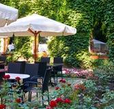 Inre för sommargatakafét i grön stad parkerar, utsmyckat med blommor och dekorativa beståndsdelar, det vita paraplyet arkivbilder