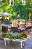 Inre för sommargatakafét i grön stad parkerar, utsmyckat med blommor och dekorativa beståndsdelar, det vita paraplyet arkivfoton