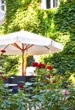 Inre för sommargatakafét i grön stad parkerar, utsmyckat med blommor och dekorativa beståndsdelar, det vita paraplyet, framdelfok arkivfoton