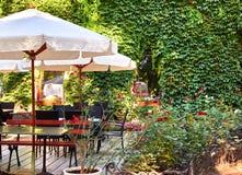 Inre för sommargatakafét i grön stad parkerar, utsmyckat med blommor och dekorativa beståndsdelar, det vita paraplyet royaltyfria foton