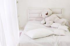 Inre för vitt rum med säng, fönstret, kuddar och björnen Arkivbild