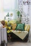Inre hörn för vardagsrum med kulöra kuddar, vaser och blommor Royaltyfria Bilder