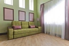 Inre i gräsplan och rosa färger färgar med den gröna soffa- och ljusparketten arkivfoto