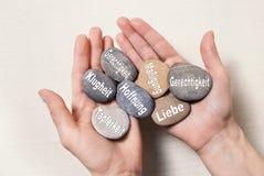 Inre jämviktsbegrepp: händer som rymmer stenar med tyska ord fo Arkivfoton