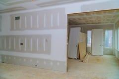 Inre konstruktion av byggprojektet med den drywall installerade dörren för ett nytt hem, innan installation royaltyfri foto