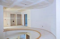 Inre konstruktion av byggprojektet med drywallen som installeras och lappas, utan applicerat att måla arkivfoto