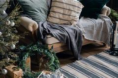 Inre lägenhet för nytt år, soffa, filt, kuddar, trädgåvor för grå skala loft arkivbilder