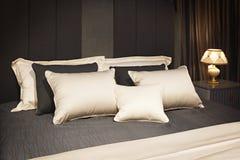 inre modernt för sovrumdesign Stor säng, rum med grå färger färgar signal, säng, textiler och kuddar i brunt-, grå färg- och beig arkivfoton