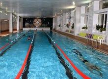 Inre offentlig inomhus simbassäng med semesterfirarefolk. Arkivfoton