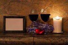 inre romantiker exponeringsglas av vin, stearinljus, hjärtor och fotoramen Arkivbilder