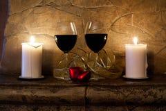 inre romantiker Två exponeringsglas av vin, stearinljus och röd hjärta för nalle Royaltyfri Fotografi