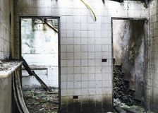 Inre sikt av ett förstört hus med belade med tegel väggar, inga dörrar och a Arkivfoto