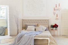 Inre sovrum i pastellfärgade ljusa färger Stor bekväm dubbelsäng i elegant klassiskt sovrum arkivbild
