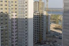 Inre ställe för många högväxta byggnader under konstruktion och kranar under en blå himmel Arkivfoton