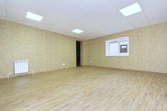 Inre tomt kontorsljusrum med den gröna tapeten som är omöblerad i en nybygge Arkivbilder