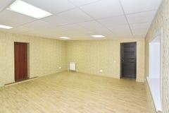 Inre tomt kontorsljusrum med den gröna tapeten som är omöblerad i en nybygge Arkivbild