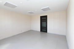 Inre tomt kontorsljusrum med den vita tapeten som är omöblerad i en nybygge Arkivbilder