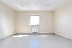 Inre tomt kontorsljusrum med den vita tapeten som är omöblerad i en nybygge Royaltyfri Bild