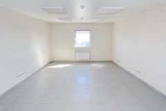 Inre tomt kontorsljusrum med den vita tapeten som är omöblerad i en nybygge Royaltyfri Fotografi