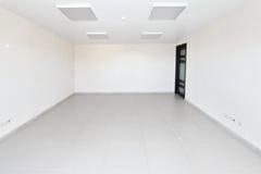 Inre tomt kontorsljusrum med den vita tapeten som är omöblerad i en nybygge Arkivfoto