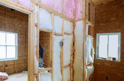Inre v?ggv?rmeisolering med mineralisk ull i tr?huset som bygger under konstruktion arkivbild