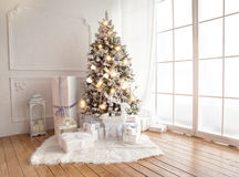Inre vardagsrum med en julgran och gåvor