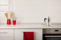 Inre vitt kök med kökhjälpmedel och röd lerkärl royaltyfria foton